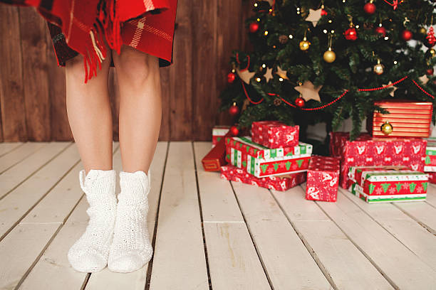 Woman standing in socks at decorated Christmas tree stock photo