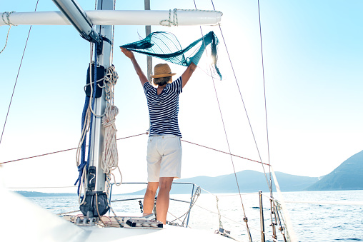 Woman standing in the breeze on a sailboat