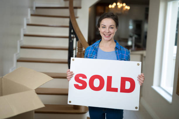 Woman standing in the living room holding sold sign stock photo