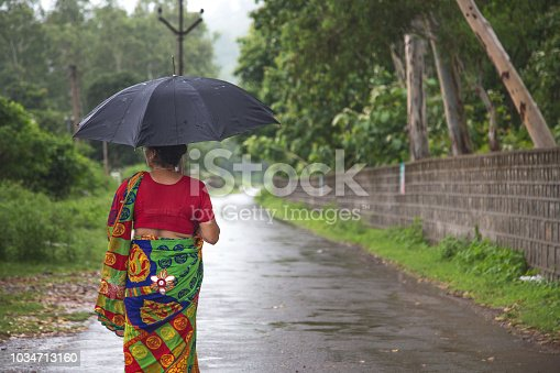 Indian women standing holding umbrella On the empty rural road in the rainy season.