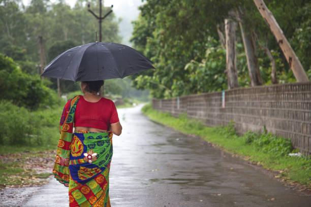Frau im Regen unter ihrem Dach – Foto