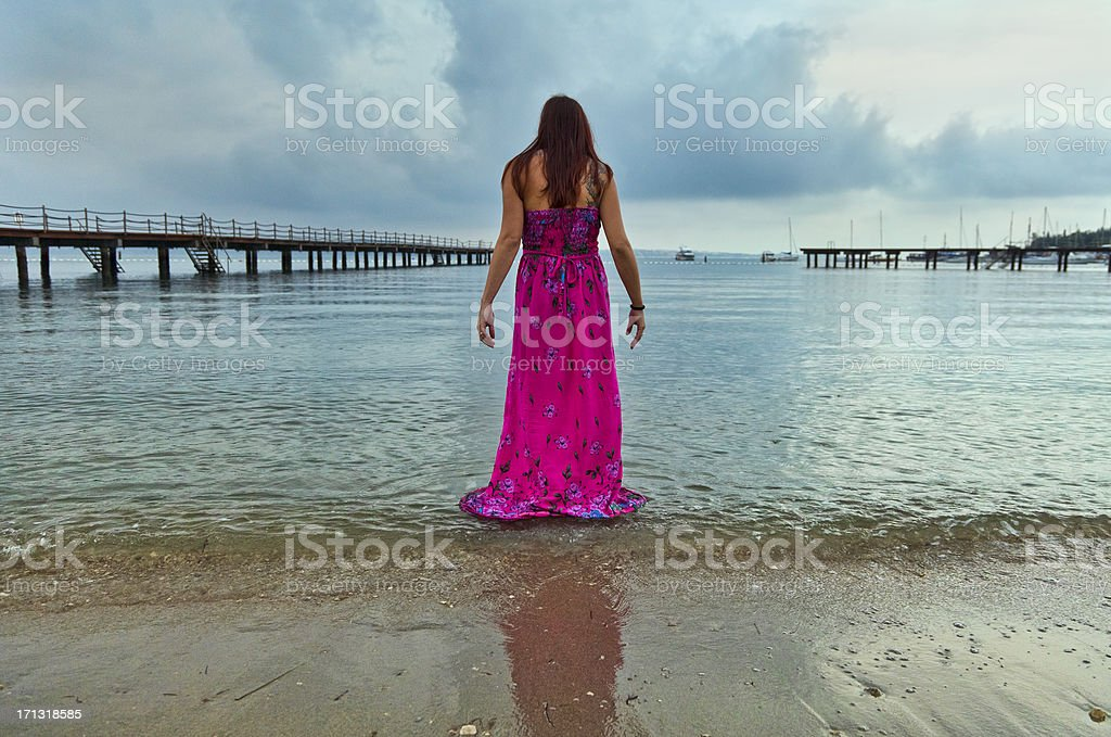 Woman standing in the sea on rainy day stock photo