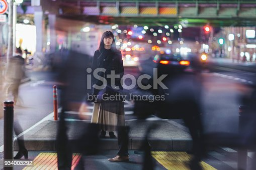 A young woman standing in the street at night in Ginza, Tokyo.