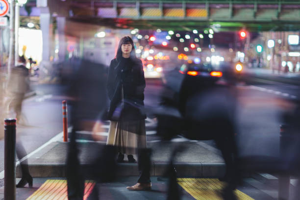 Woman standing in the street at night in Tokyo A young woman standing in the street at night in Ginza, Tokyo. long exposure stock pictures, royalty-free photos & images