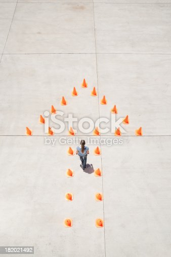 istock Woman standing in traffic cones forming arrow  182021492