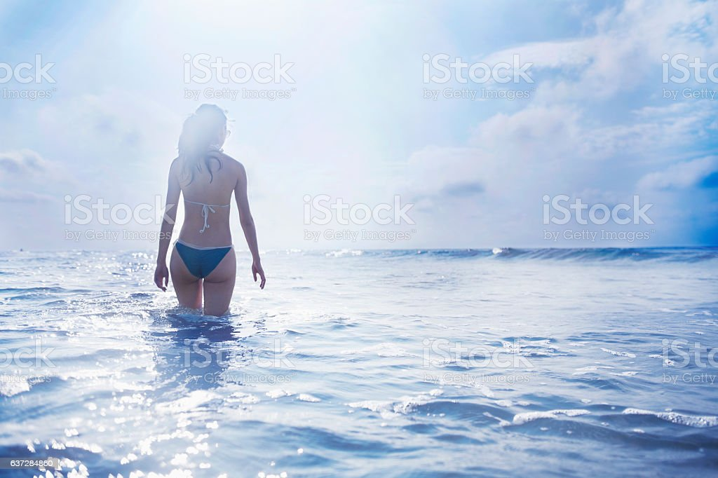 Woman standing in waves at beach stock photo