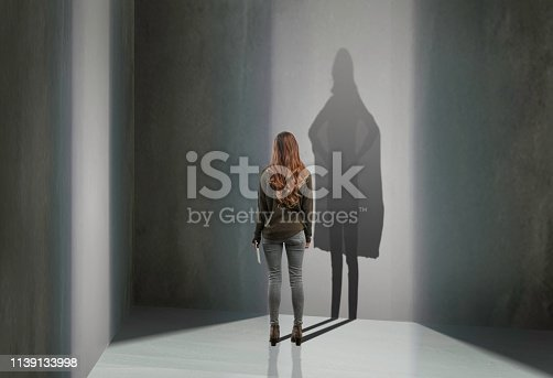 Woman standing in with superhero shadow