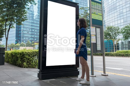 istock Woman standing near blank advertising lightbox on the bus stop, mock up 1174817650