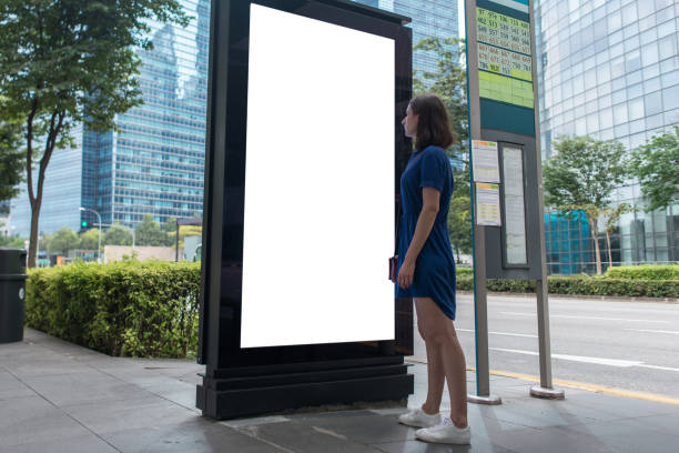 Woman standing near blank advertising lightbox on the bus stop, mock up stock photo