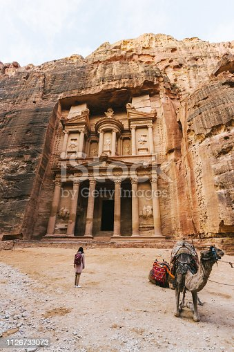 Young Caucasian woman standing near camel infront of Al-Khazneh in Petra
