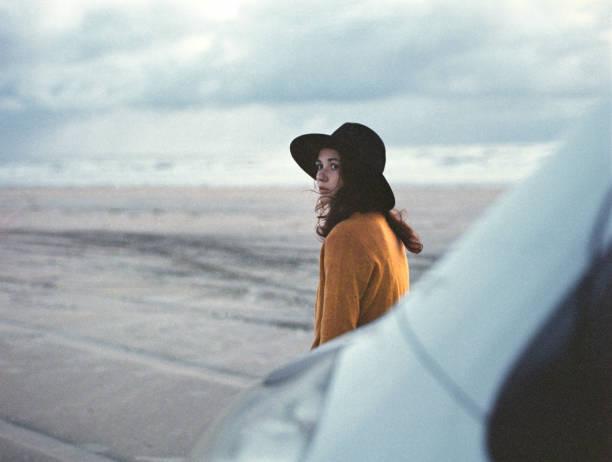 Woman standing near camper van   on beach in Denmark stock photo