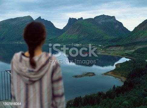 Young Caucasian woman in hat standing  near fjord in village in Lofoten Islands