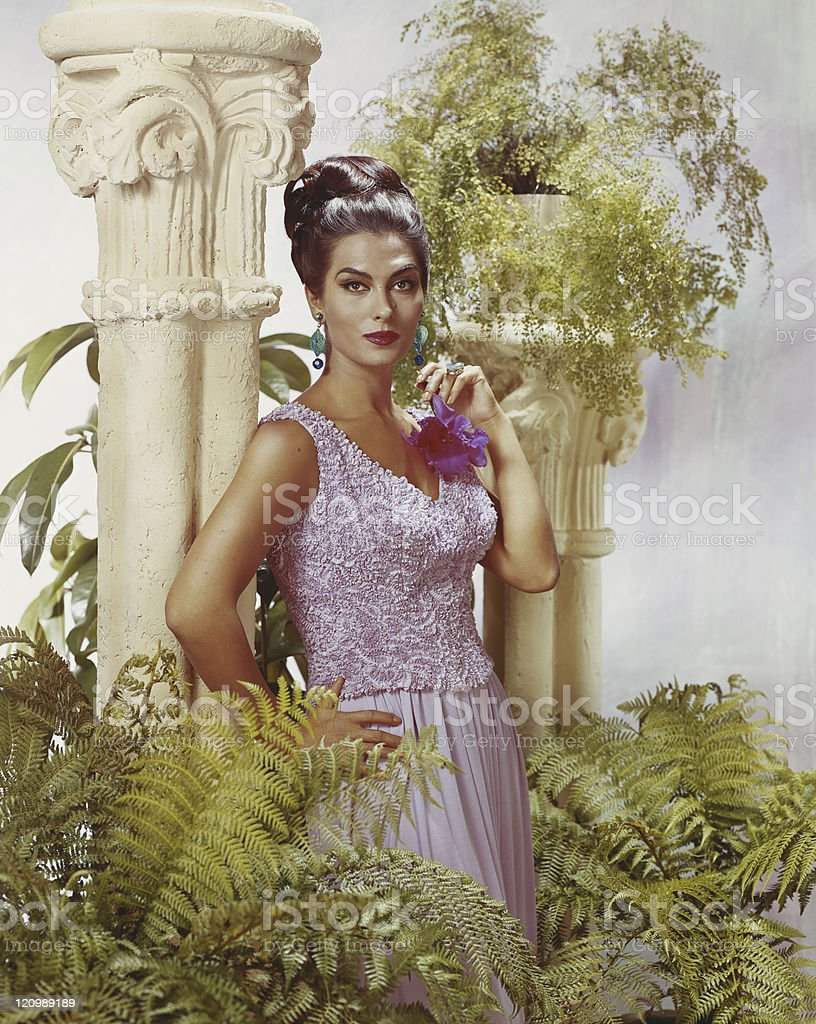 Woman standing near pedestal and pot plants, portrait royalty-free stock photo