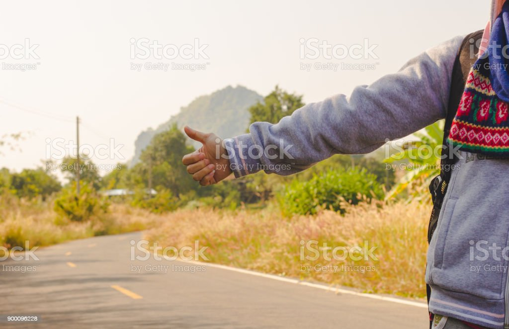 woman standing near road way with hand autostop outdoor stock photo