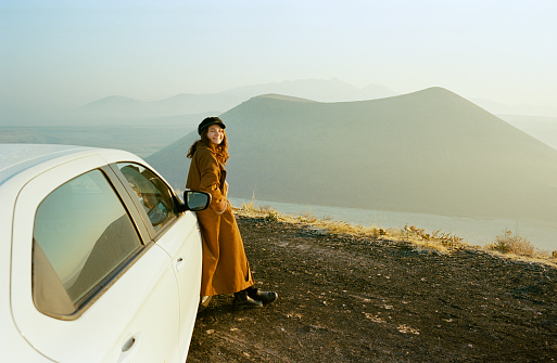 Young Caucasian woman standing near the car and looking at volcano