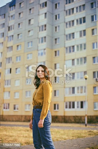 istock Woman standing near the  colorful building 1204577560