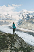 Young Caucasian woman looking at the scenic view of  the glacier in Swiss alps in Gornergrat