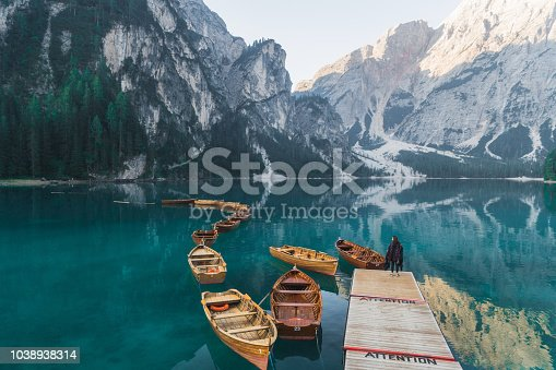 Young Caucasian woman in plaid  standing near the lake Lago di Braies  in Dolomites