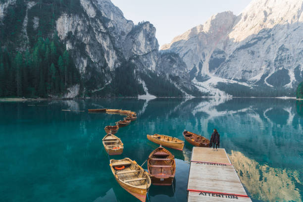 woman standing near the lake lago di braies  in dolomites - latemar foto e immagini stock