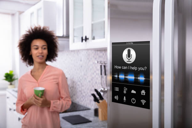 woman standing near the refrigerator with voice recognition - intelligence stock pictures, royalty-free photos & images