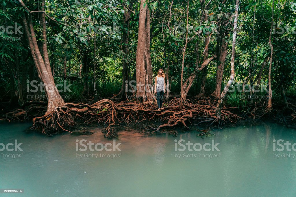 Woman standing near the river in tropical forest stock photo