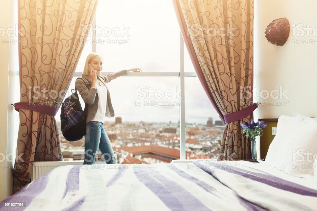 Daybreak at hotel room. Young female traveller watching cityscape,...