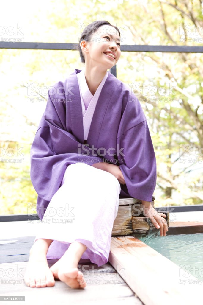 Woman standing next to an open-air bath royalty-free stock photo