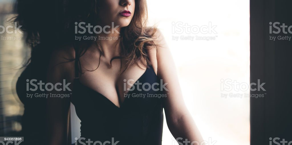 Woman standing next to the open window and enjoying in beautiful day. stock photo