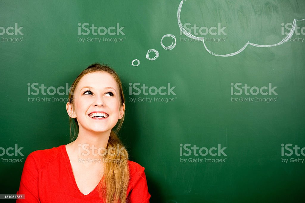Woman standing next to thought bubble on blackboard stock photo