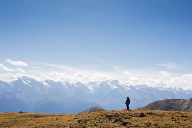 Frau steht auf einer Klippe hoch oben in den Bergen – Foto