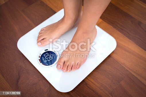 istock Woman standing on a digital scale with body fat analyzer 1134138269