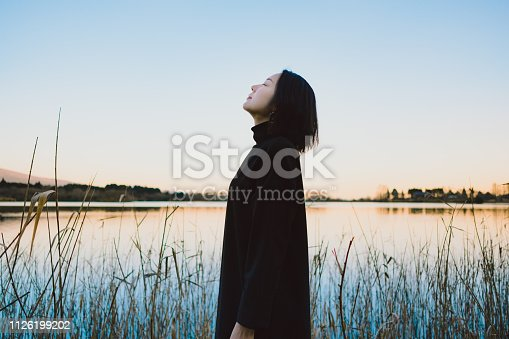 A woman standing on a lakeside.