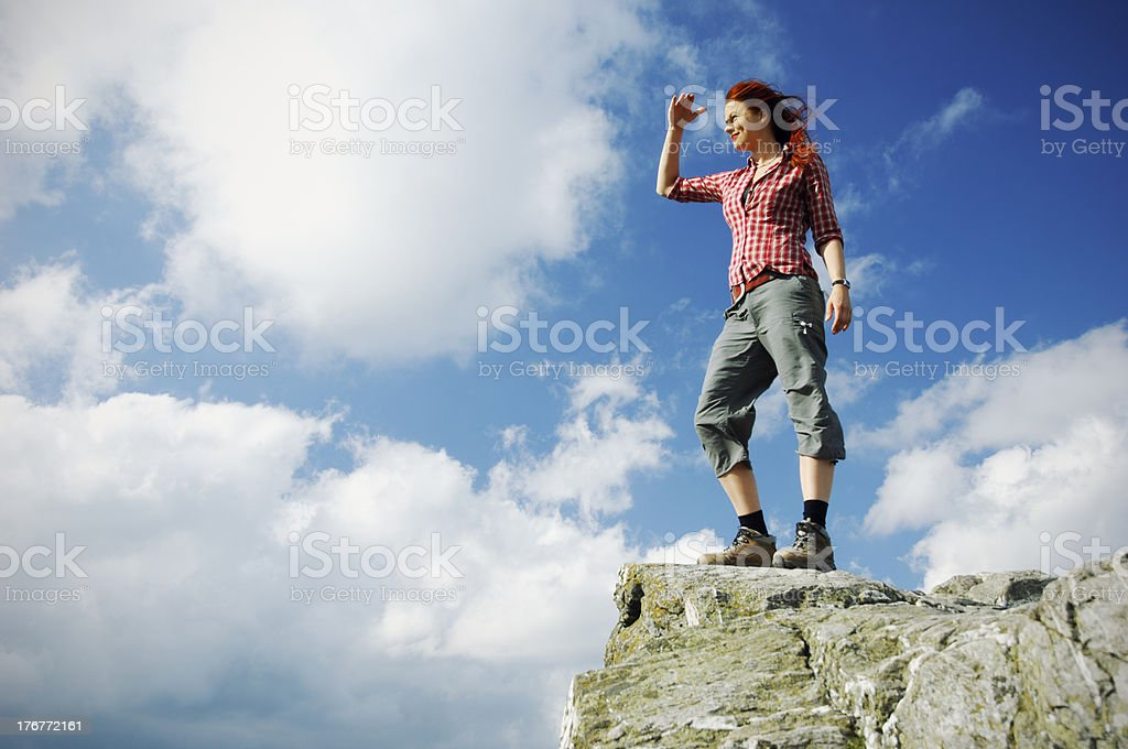 Woman standing on a mountain and gazing in the distance royalty-free stock photo