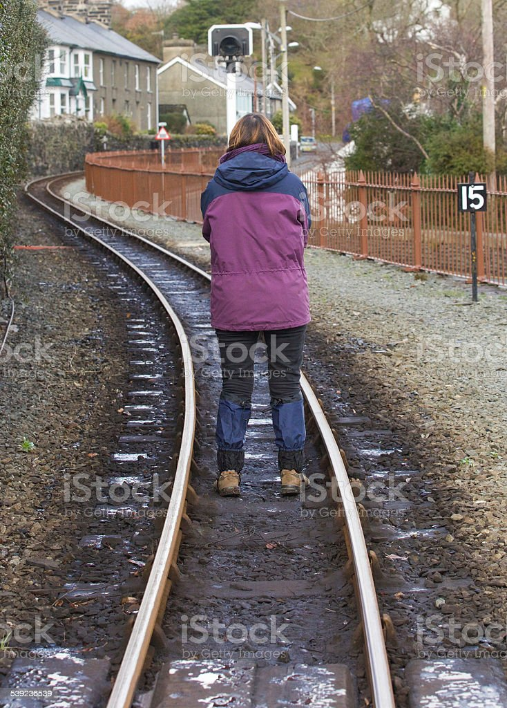 Mujer de pie en un vías de ferrocarril brazos doblado hacia de distancia foto de stock libre de derechos