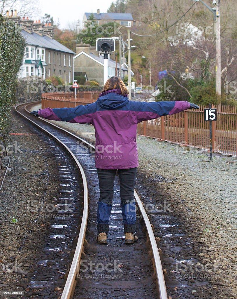 Mujer de pie en un vías de ferrocarril brazos, abierto foto de stock libre de derechos
