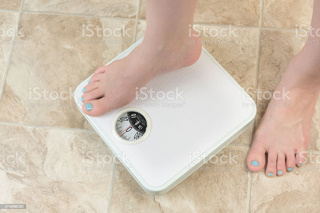 woman standing on a weight scale stock photo