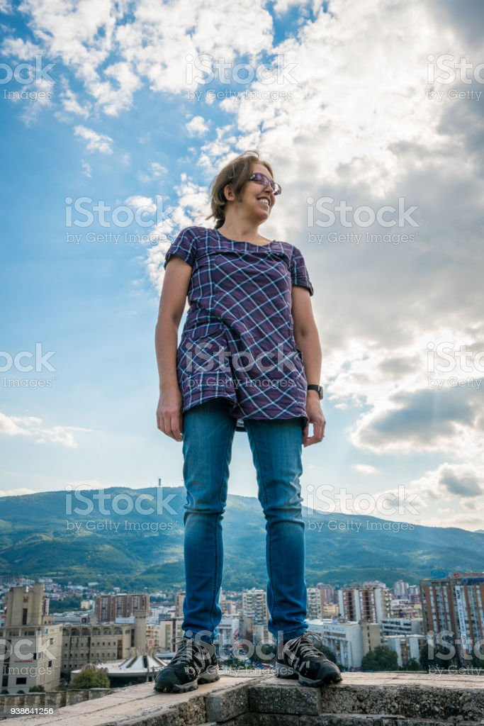 Woman standing on ancient wall with the city of Skopje in the background. stock photo