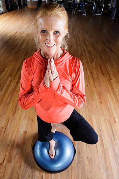 Woman Standing on Balance Ball in Health Club stock photo