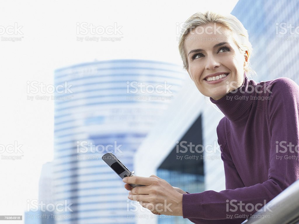 Woman standing on balcony with cellular phone royalty-free stock photo