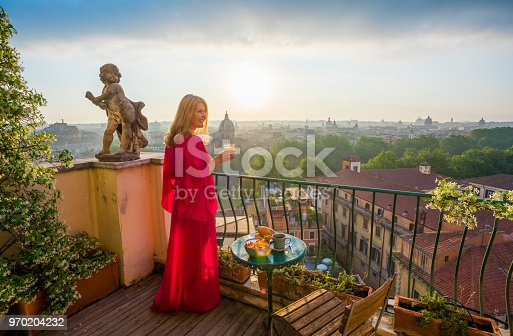 Female standing on romantic balcony with glass of fresh orange juice