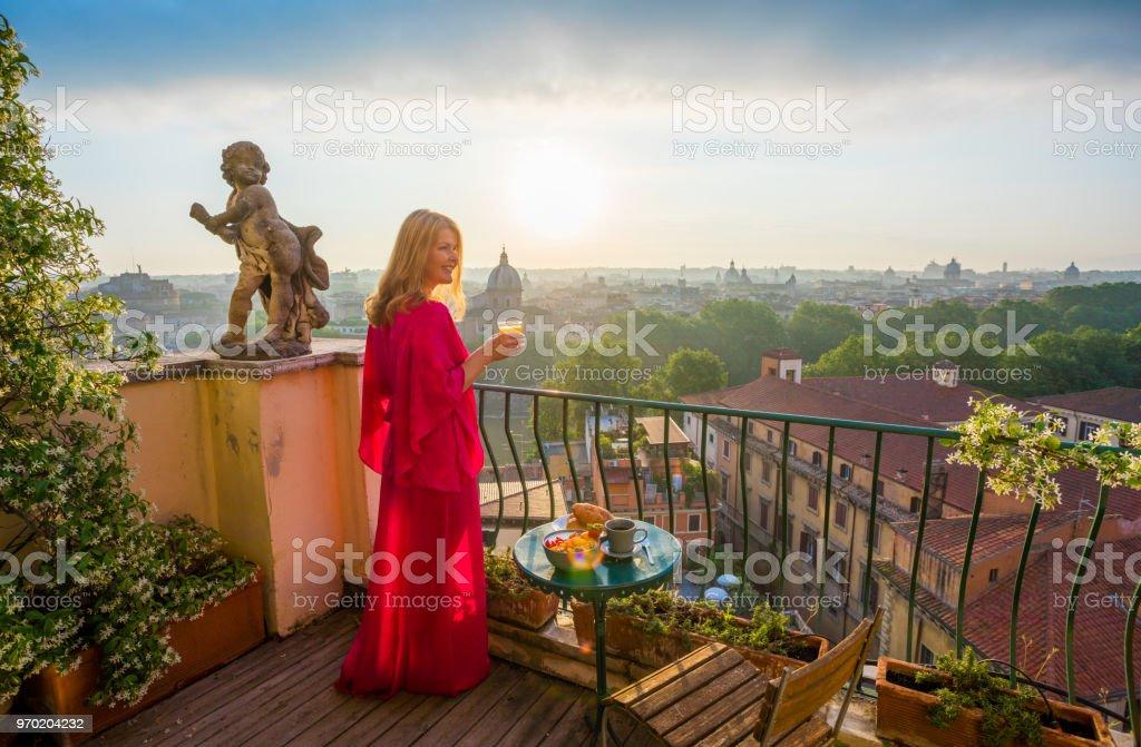 Mujer de pie en el balcón con vaso de zumo de naranja - foto de stock
