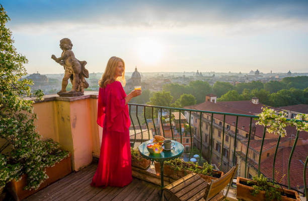 woman standing on balcony with glass of fresh orange juice - vacations food stock pictures, royalty-free photos & images