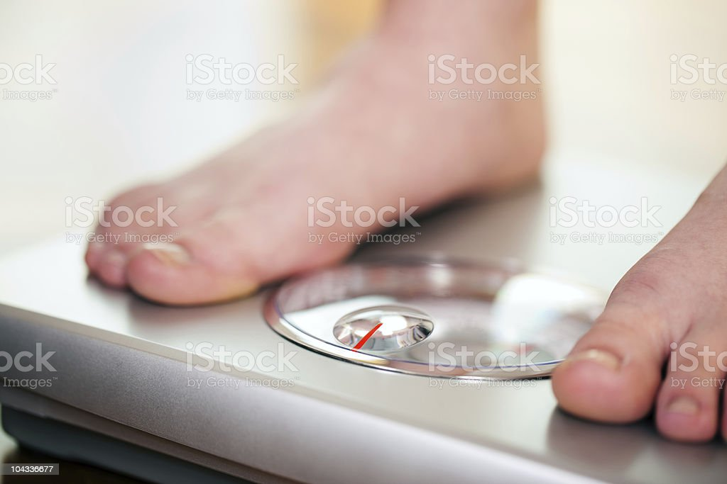 Woman standing on bathroom scale royalty-free stock photo
