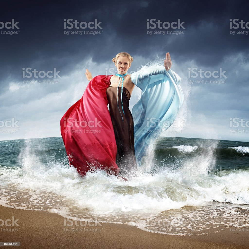 Woman Standing on Beach Commanding Dark Sky and Waves royalty-free stock photo