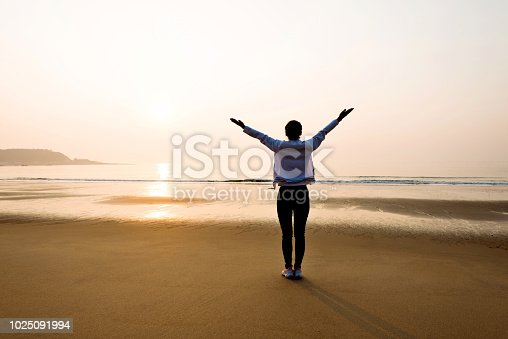 istock Woman standing on beach with arms raised 1025091994