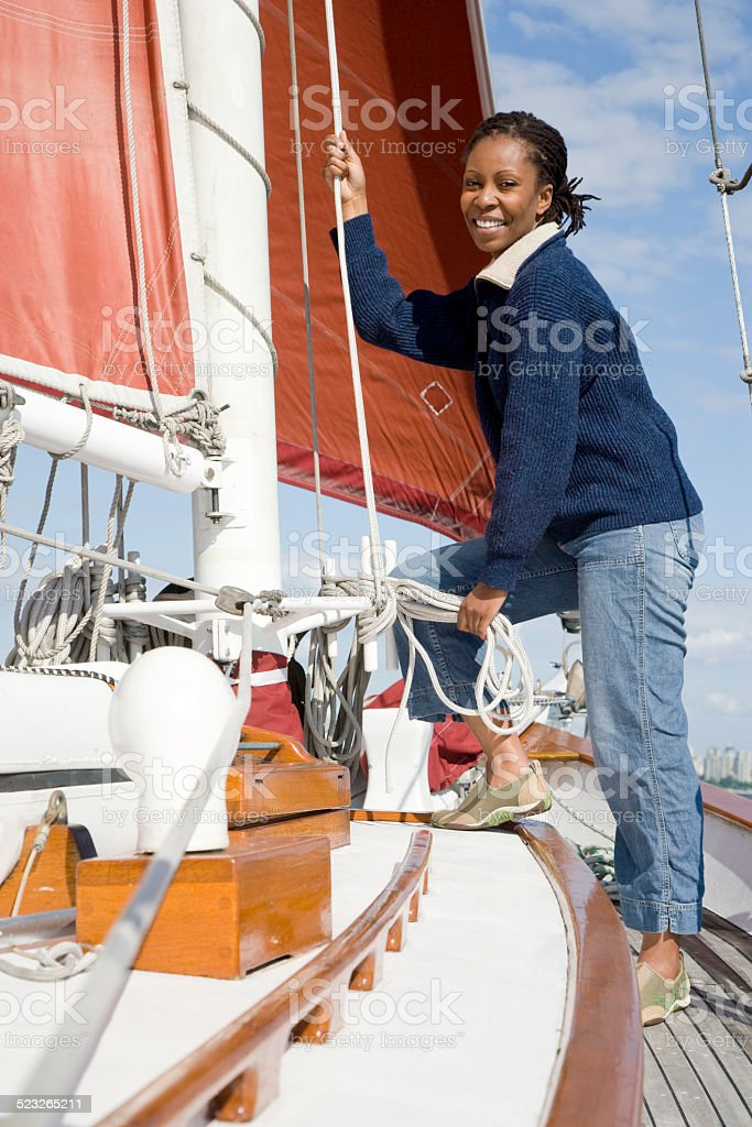Woman Standing on Boat Holding Rope stock photo