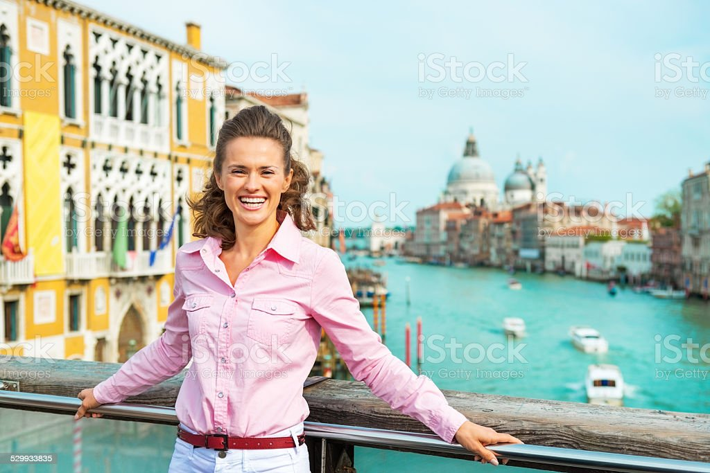 Woman standing on bridge with grand canal view in venice stock photo
