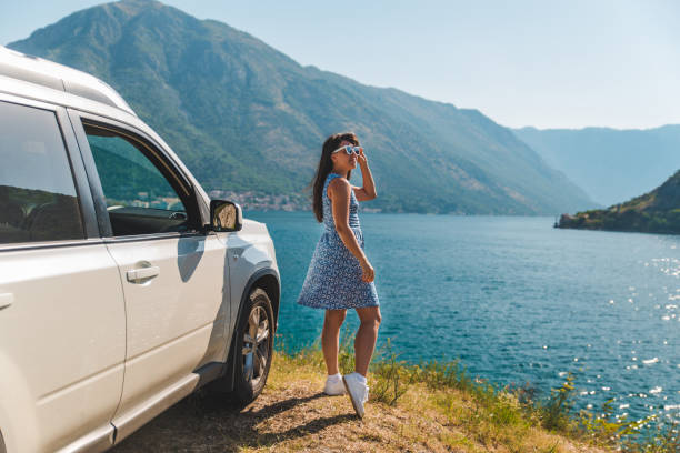 woman standing on cliff near white suv car with beautiful view of sea bay with mountains stock photo