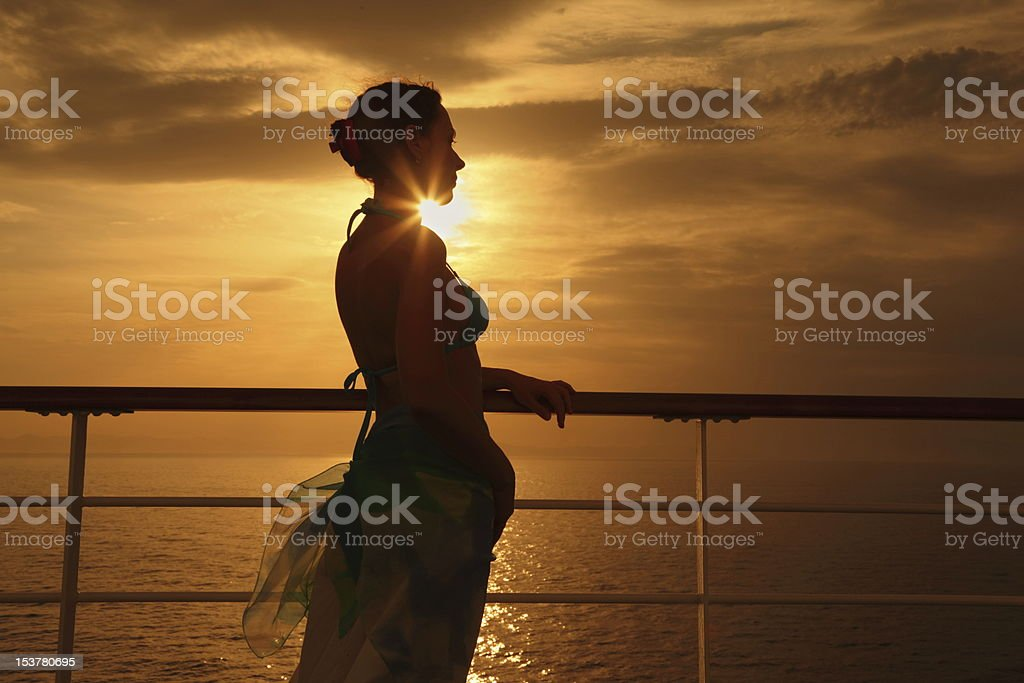 Woman standing on deck of cruise ship and looking away. royalty-free stock photo