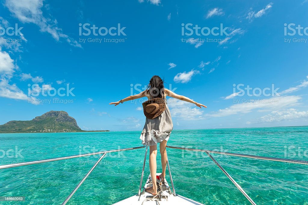 Woman standing on edge of ship wanting to fly stock photo